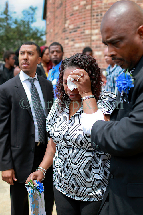 14 May 2014. New Orleans, Lousiana. <br /> Sabrina Jackson is devastated as she leaves the funeral of her 14 year old son Miqual Jackson at the New Hope Baptist Church. Miqual Jackson was shot in the back of the head May 5th and died shortly afterwards. Surviving brother Lamichael was shot in the leg. 52 year old Gregory Johnson is wanted on 1st degree murder charges. Randy Pittman, 49, an associate of Johnson's was arrested on 3 counts of being a principal to 1st degree murder. The New Hope Baptist Church witnessed the funeral of 1 year old Londyn Samuels who was also gunned down in cold blood on the streets of New Orleans 8 months ago..<br /> Charlie Varley/varleypix.com