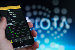 An iPhone is seen with a bitcoin price graph and the logo of the new IOTA currency in the background in this photo illustration on December 15, 2017. Bitcoin has been scrutinised recently for its difficulty in scaling, its costly transactions and lenghty confirmation times. With its new DAG technology IOTA overcomes these hurdles. (Photo by Jaap Arriens/Sipa USA)
