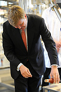Prins Willem-Alexander tijdens de opening van het Europese Heinz Innovatie Centrum in Nijmegen. In dit onderzoekscentrum werken produktontwikkelaars en voedingswetenschappers aan de nieuwste ontwikkelingen op het gebied van voeding en verpakkingen voor de Europese markt. <br /> <br /> Prince Willem-Alexander during the opening of the European Heinz Innovation Centre in Nijmegen. In this research work product developers and nutrition scientists at the latest developments in the field of nutrition and packaging for the European market.<br /> <br /> Op de foto / On the photo:  Prins Willem Alexander vult een flesje ketchup , en legt deze op zijn kant ( truukje uit zijn schooltijd )<br /> <br /> Prince Willem Alexander fills a bottle of ketchup, and places it on its side (trick from his school time )