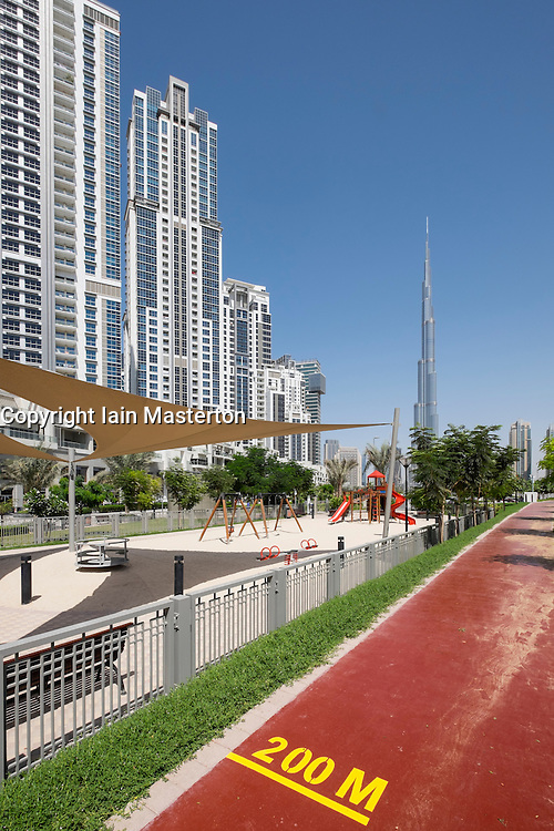 Park and running track at  Bay Avenue residential property development and Burj Khalifa in Business Bay district of Dubai United Arab Emirates