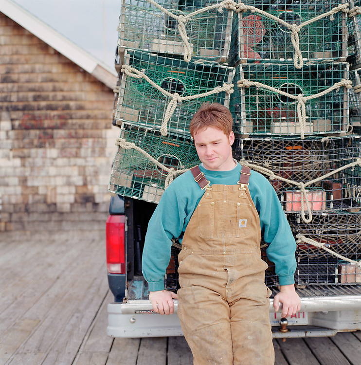 Portrait of a commercial fisherman in Nahant, Massachusetts in front of lobster traps on his truck parked at the dock.