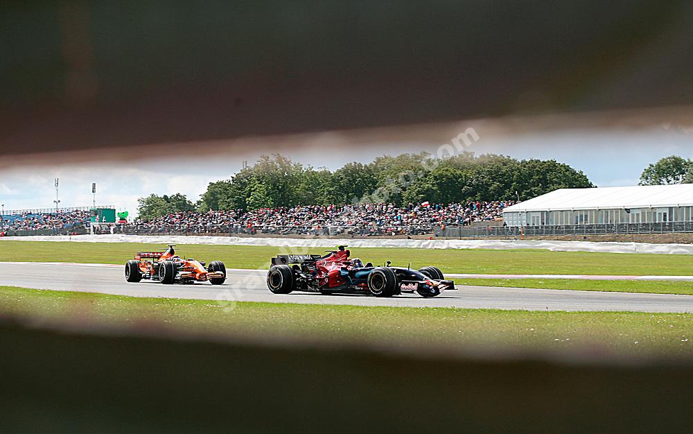 Scott Speed (Toro Rosso-Ferrari) in front of Christijan Albers (Spyker-Ferrari) shot through an armco in practice for the 2007 British Grand Prix at Silverstone. Photo: Grand Prix Photo