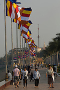 """30 JANUARY 2013 - PHNOM PENH, CAMBODIA:   People walk along Sisowath Quay in Phnom Penh where flags at half mast for late Cambodian King Norodom Sihanouk. Sihanouk (31 October 1922- 15 October 2012) was the King of Cambodia from 1941 to 1955 and again from 1993 to 2004. He was the effective ruler of Cambodia from 1953 to 1970. After his second abdication in 2004, he was given the honorific of """"The King-Father of Cambodia."""" Sihanouk held so many positions since 1941 that the Guinness Book of World Records identifies him as the politician who has served the world's greatest variety of political offices. These included two terms as king, two as sovereign prince, one as president, two as prime minister, as well as numerous positions as leader of various governments-in-exile. He served as puppet head of state for the Khmer Rouge government in 1975-1976. Most of these positions were only honorific, including the last position as constitutional king of Cambodia. Sihanouk's actual period of effective rule over Cambodia was from 9 November 1953, when Cambodia gained its independence from France, until 18 March 1970, when General Lon Nol and the National Assembly deposed him. Upon his final abdication, the Cambodian throne council appointed Norodom Sihamoni, one of Sihanouk's sons, as the new king. Sihanouk died in Beijing, China, where he was receiving medical care, on Oct. 15, 2012. His cremation is scheduled to take place on Feb. 4, 2013. Over a million people are expected to attend the service.        PHOTO BY JACK KURTZ"""