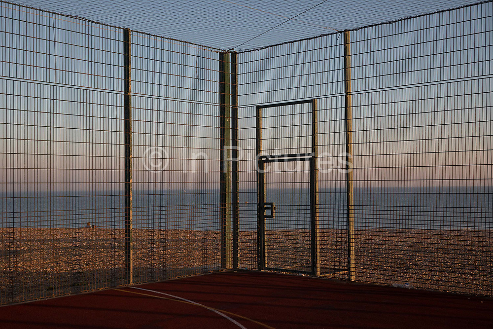 Sundown at a beachfront basketball court on the 20th April 2019 in Hastings in the United Kingdom. Hastings is a town on England's southeast coast, its known for the 1066 Battle of Hastings.