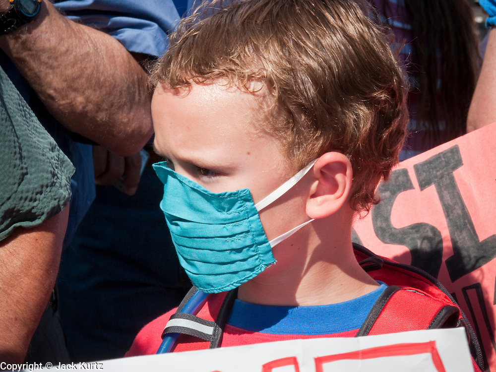 Aug. 8, 2009 -- SCOTTSDALE, AZ: A boy wears a breathing filter during a protest against the Obama health care reforms in Scottsdale, AZ, Saturday. Nearly 1,000 people opposed to the President Barack Obama's health care reform efforts picketed the offices of Congresman Harry Mitchell (D-AZ) in Scottsdale, AZ, Saturday. The protest was organized by conservative groups who are organizing similar protests against President Obama across the US. Ostensibly concerned mostly with health care reform, it was also a protest against almost everything related to the Obama administration. Photo by Jack Kurtz / ZUMA Press