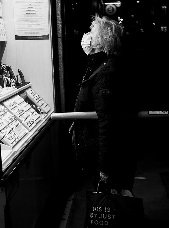 A lady wearing a mask looks into the display of a jewellery shop on the high street in Cheltenham, England on the night before the second national lockdown in the UK on the 3rd November, 2020.