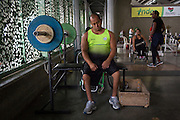 """2016/03/10 – Medellin, Colombia: Joe Gonzalez Bettencourt, 38, tries to relax after some weight lifting exercises in the gymnasium at Atanasio Girardot Stadium, Medellin, 10th March, 2016. <br /> -<br /> Joe was a teenager when a paramilitary group approached him and his friends to become part of the Bloque Cacique Nutibara gang by starting to steal and kill. Joe and his friends refused because they didn't like violence and were more interested in party and living a life like any other normal teenager. But that refuse came with a high price. Joe and his best friend were chased on motorbike and the gang shot them. Joe was hit twice, one bullet hit his neck and another bullet hit his abdomen leaving through the lower back, making him paraplegic. His friend died. <br /> At the time of the incident, Joe was trying to become a football player, so sports were always part of his life. When he understood that he would be on a wheel chair he took on sports to keep going with his life. He started to play basketball, then tennis and in both he was National Champion. It was through his wife, who also is a Paralympics athlete, that he became interested in weigh throwing and javelin. On Joe's second tournament he became national champion, a title that he still holds today. During his progression on the sport he reached 4th in the world. Joe qualified to the Rio 2016 Paralympic games, but due to quota places he might not be able to go, something that he feels is quite unfair after so much work. <br /> Asked about his feeling for the responsible people that shot him, he says, """"We must be peaceful, forgive, but never forget. I will never forget because everyday I have to sit on this chair"""". (Eduardo Leal)"""