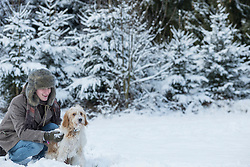 Young man with dog in snowy landscape in winter, Bavaria, Germany