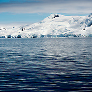 Snow and ice-covered mountains line the coast along the western side of the Antarctic Peninsula.