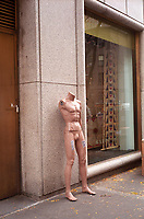 A mannequin, stripped bare, stands lonely and discarded  outside a store on Madison Avenue, New York City.