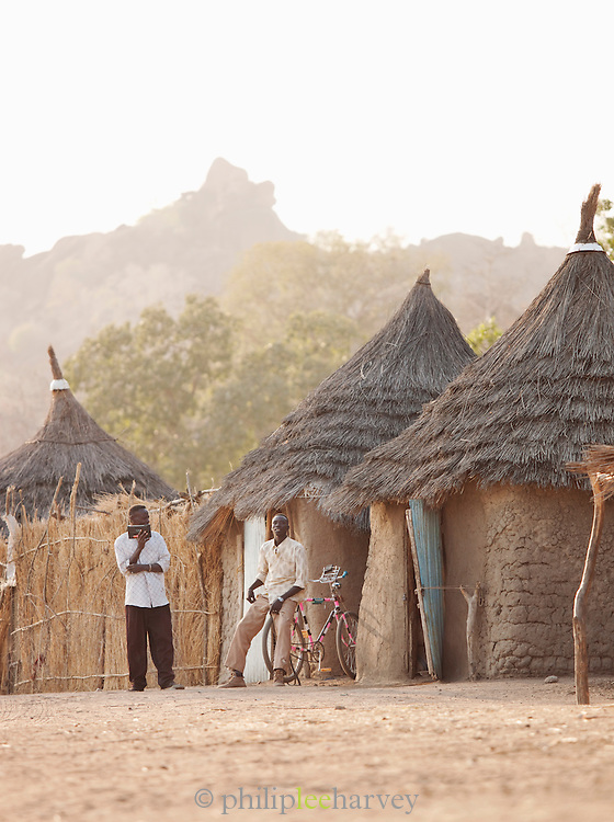 Young men of the Nuba tribe sit outside listening to music on a radio, Nyaro village, Kordofan region, Sudan