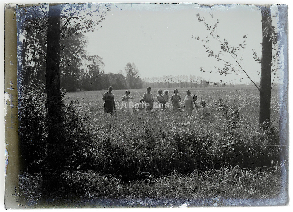 1900s glass plate with family standing in open field