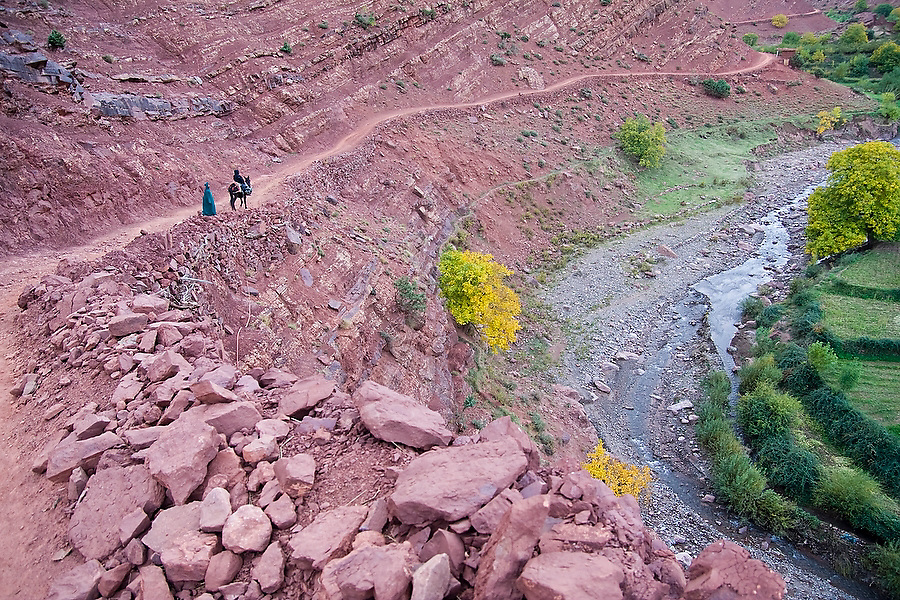 A Berber man accompanies American tourist Liana Welty riding a mule along a dirt road in a dramatic river canyon between Abachkou and Rougoult in the M'Goun Massif, Central High Atlas, Morocco on November 4, 2007.