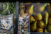 Detail of supermarket packaging and assorted materials being stored in bins outside a local Co-Op in Bellingham, on 5th February 2020, in London, England. The industrial bins are parked in front of the supermarket posters that shows fresh fruit of cabbages and pears, and have been wrapped in plastic cling-film to contain the many boxes stacked up and awaiting collection by a recycling provider.