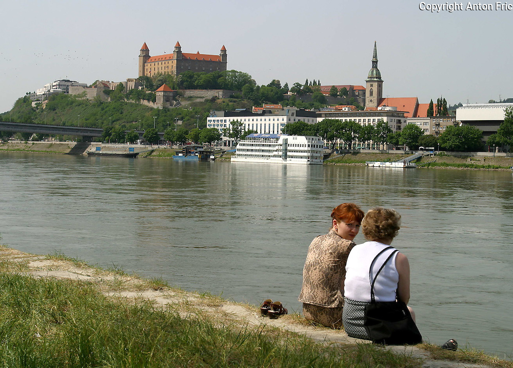 People relaxing at the right bank of river Danube in Bratislava with a view of Bratislava castle on the other side.