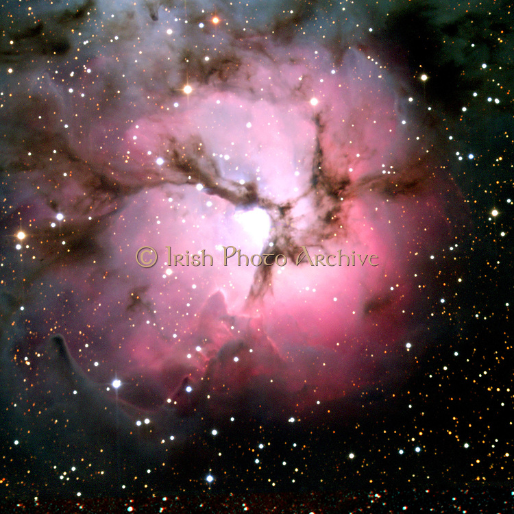 Spitzer Space Telescope composite comparison visible-light and infrared views  of the glowing Trifid Nebula, a giant star-forming cloud of gas and dust located in the constellation Sagittarius. Credit NASA. Science Astronomy