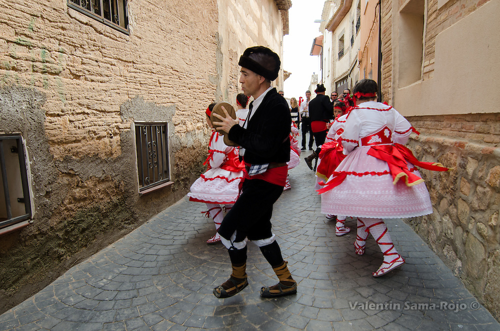 Dancers dressed with traditional red dress lead by the 'Mayoral' during a turn as they dance in a narrow street of Cetina.