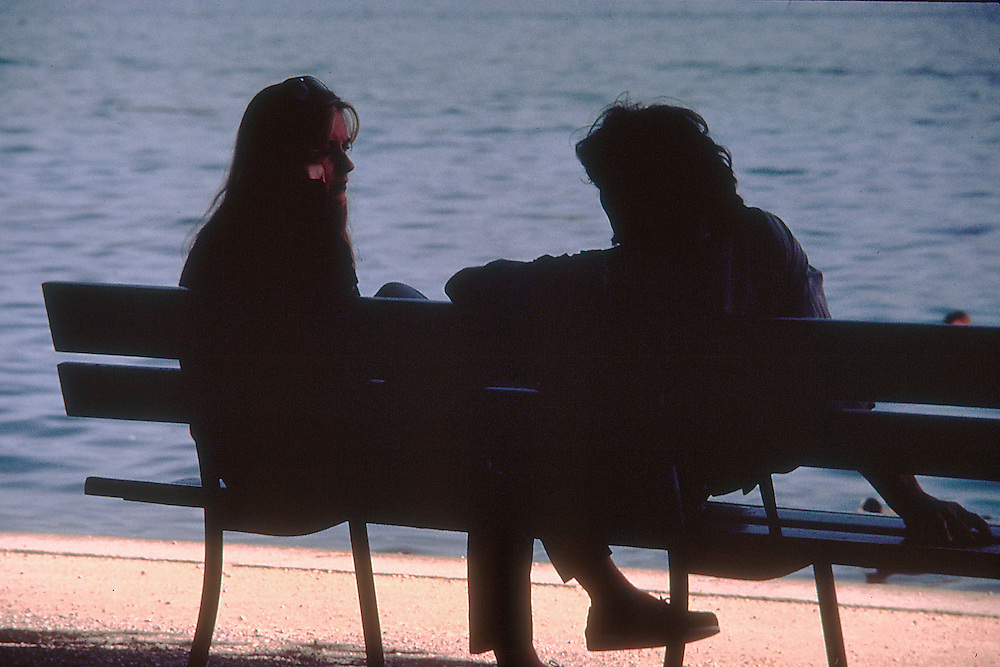 Silhouettes of a man and a woman, couple, maybe lovers, sitting on a park bench in front of Lake Lucerne, Switzerland having a relaxing conversation.