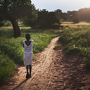 A girl heads home in the dying light in rural Makurdi in Benue State, Nigeria. Benue state has one of the highest HIV prevalence in Nigeria and the charity EVA target vulnerable children who would otherwise miss out of being tested for HIV and therefor not know their HIV statues.