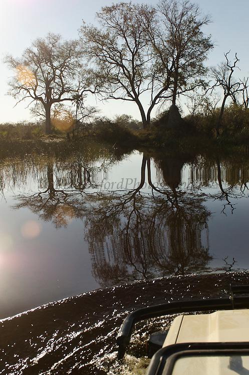 Tourist Game Vehicle traversing flood waters<br /> Moremi Game Reserve, Okavango Delta<br /> BOTSWANA