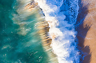 Aerial photograph looking straight down at a wave breaking off of Kepuhi Beach, West Molokai, Hawaii