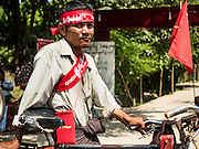 01 NOVEMBER 2015 - YANGON, MYANMAR: A man wearing a NLD / Aung San Suu Kyi headband and sash pushes his bicycle to the NLD's last election rally of the 2015 election in the Yangon suburbs Sunday. Political parties are wrapping up their campaigns in Myanmar (Burma). National elections are scheduled for Sunday Nov. 8. The two principal parties are the National League for Democracy (NLD), the party of democracy icon and Nobel Peace Prize winner Aung San Suu Kyi, and the ruling Union Solidarity and Development Party (USDP), led by incumbent President Thein Sein. There are more than 30 parties campaigning for national and local offices.    PHOTO BY JACK KURTZ