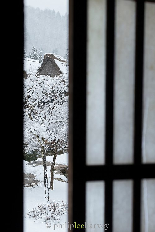Covered in snow houses seen through door, Shirakawa-go, Japan