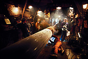 """Working in the Arctic darkness, welders are sheltered by a """"push shack"""" with electric heaters to shield them from the sub-zero temperatures ¾ cold so severe that it contributed to some of the nearly 4,000 welding flaws that had to be repaired before oil flowed down the Trans-Alaska Oil Pipeline in 1977.  © Steve Raymer / National Geographic Creative"""