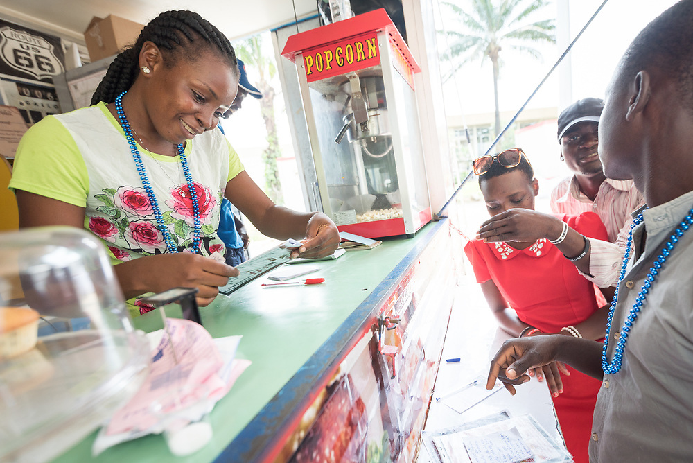 """6 December 2017, Abidjan, Côte d'Ivoire: Zainab (left) from Côte d'Ivoire takes orders, as a food truck, named """"Bon Appetit"""" parked near the Global Village provides food to participants in ICASA 2017. The 19th International Conference on AIDS and STIs in Africa (ICASA) 2017 gathers thousands of researchers, medical professionals, academics, activists and faith-based organizations from all over the world, all looking to overcome the HIV epidemic and eliminate AIDS as a public health threat."""