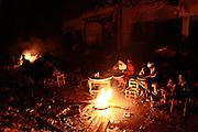 Woman gather next to a fire amid destroyed buildings due to the Jan.12 earthquake in downtown Port-au-Prince, Haiti, Feb. 5,  2010. (AP Photo/Rodrigo Abd)