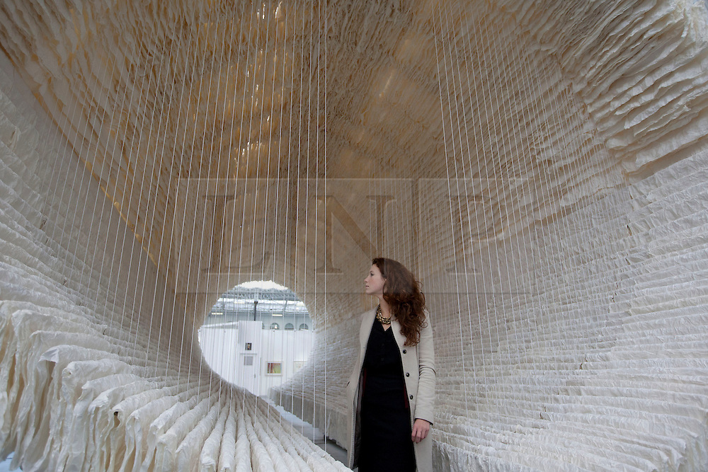 © Licensed to London News Pictures. 28/02/2013. London, UK. A visitor to the Art13 London art fair views 'Boat' a 12 metre art installation made from rice paper by Chinese artist Zhu Jinshi in London today (28/02/2013).  The installation, presented by Pearl Lam Galleries forms the centre piece for the Art12 London art fair which starts on the 28th of February at London Olympia. Photo credit: Matt Cetti-Roberts/LNP