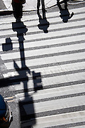 shadows of two people waiting to cross the road