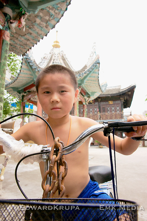 Young boy on a bike in the courtyard of a temple.