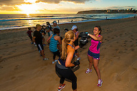 A fitness class practices boxing at sunrise, Manly Beach, Sydney, New South Wales, Australia