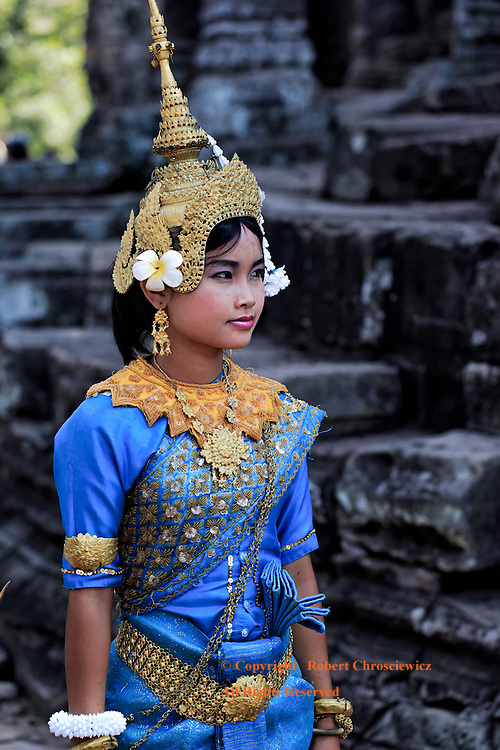 Khmer Beauty: A beautiful young lady dancer, dressed in the traditional Khmer fashion, awaits her cue amongst the ruins of Bayon Angkor Thom, Siem Reap Cambodia.