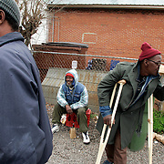 """Locals hang out in the """"ghetto"""" part of Augusta, Georgia near the projects. Butler Nero, on crutches, Charles Hill (hooded sweatshirt) and Robert Frederick, drink beer and talk about their neighborhood."""