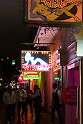 Group of tourists in crowded street scene in famous Bourbon Street in French Quarter of New Orleans, USA