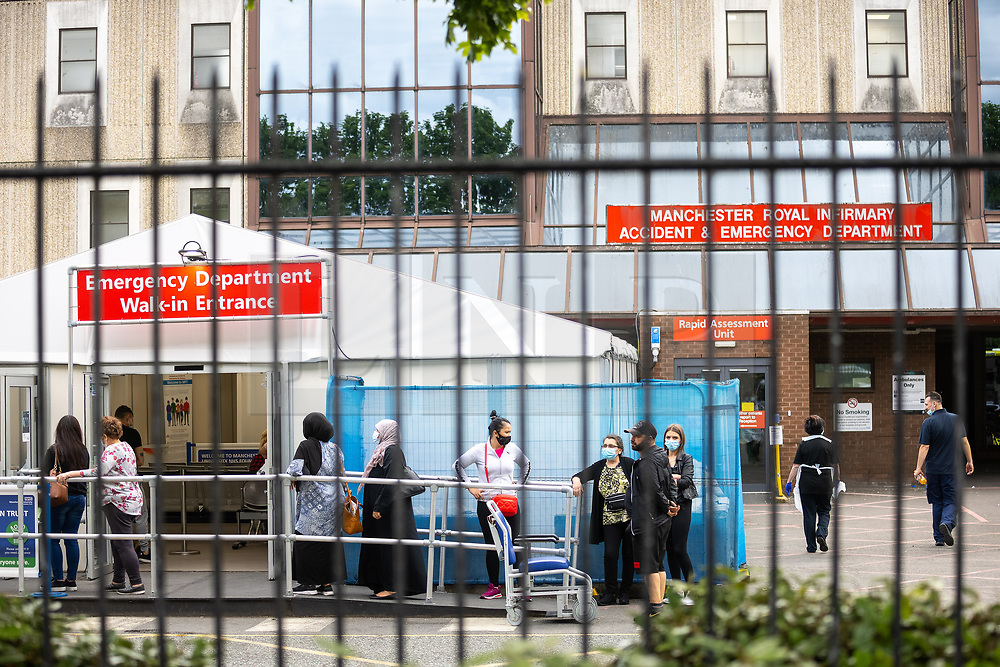 © Licensed to London News Pictures. 09/06/2021. Manchester, UK. NB PHOTOGRAPH TAKEN FROM A PUBLIC LOCATION THROUGH A CAR PARK FENCE - QUEUING PATIENTS' FACES ARE VISIBLE . People queue outside a tent in front of the entrance to the Accident and Emergency department at Manchester Royal Infirmary . Photo credit: Joel Goodman/LNP