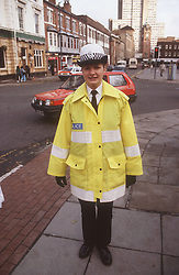 Female community police officer standing in street wearing fluorescent coat,