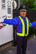 A traffic warden directing traffic and pedestrians. Tokyo, Japan
