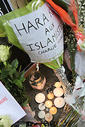 """Flowers and candles are placed in memorial for colleagues and friends. French journalists make a vigil in central Paris next to the Offices of Charlie Hebdo, marking one minute silence at midday, to mourn the death of their colleages. Ten staff including journalists, cartoonists and editors at Charlie Hebdo were killed the day before, when armed gunmen attacked the offices of Charlie Hebdo, killing twelve people including two policemen; four more are in critical condition. It is the deadliest terror attack in France for over fifty years. Charlie Hebdo is a satirical publication well known for its political cartoons. The newspaper had been threatened for making satirical images of the prophet Muhammad.<br /><br />Islamist offerings and Arabic writing wishes to Charlie Hebdo<br /><br />As a solidarity action with the deaths at Charlie Hebdo many placards read """"Je suis Charlie"""" translating as """"I am Charlie (Hebdo)"""". Demonstrators hold aloft pens, brushes and crayons, in solidarity for their dead colleagues, symbolizing the profession of journalists and cartoonists who were killed. Many pens and candles have been placed in shrines throughout the city."""