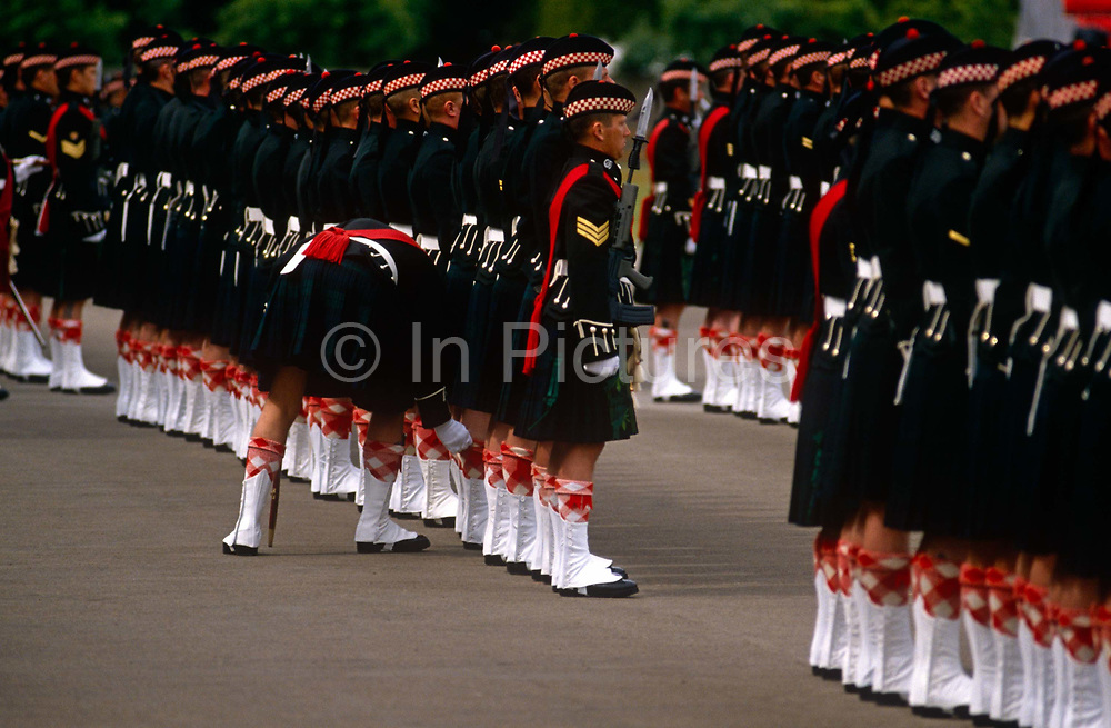 An officer bends down to inspect a soldier within a battalion of Argyll and Sutherland Highlanders regiment of the British Army, before a parade in front of Queen Elizabeth the Queen at the regiment's Edinburgh base at Redford Barracks, Scotland. The regimented rows and columns form a disciplined line-up of troops. The Argyll and Sutherland Highlanders (Princess Louise's) was an infantry regiment of the British Army until amalgamation into The Royal Regiment of Scotland in 2006. The regiment was created in 1881 as an amalgamation of the 91st and 93rd Regiments of Foot going on to serve in the First and Second World Wars, Korea, Aden. It was announced in 2004 as part of the restructuring of the infantry that the Highlanders would be amalgamated with the other Scottish infantry regiments into a single seven battalion strong Royal Regiment of Scotland.