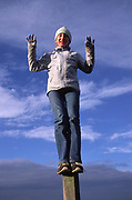 ARM4CD Child standing on fence post against blue cloud sky background