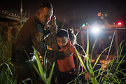 U.S. Border Patrol agent Carlos Ruiz helps asylum-seeking migrant families unload from a U.S. Border Patrol riverine unit after they were rescued during an attempted crossing of the Rio Grande in Hidalgo, Texas, U.S., August 23, 2019.