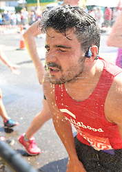 A runner uses a shower to cool off during the 2018 Virgin Money London Marathon.