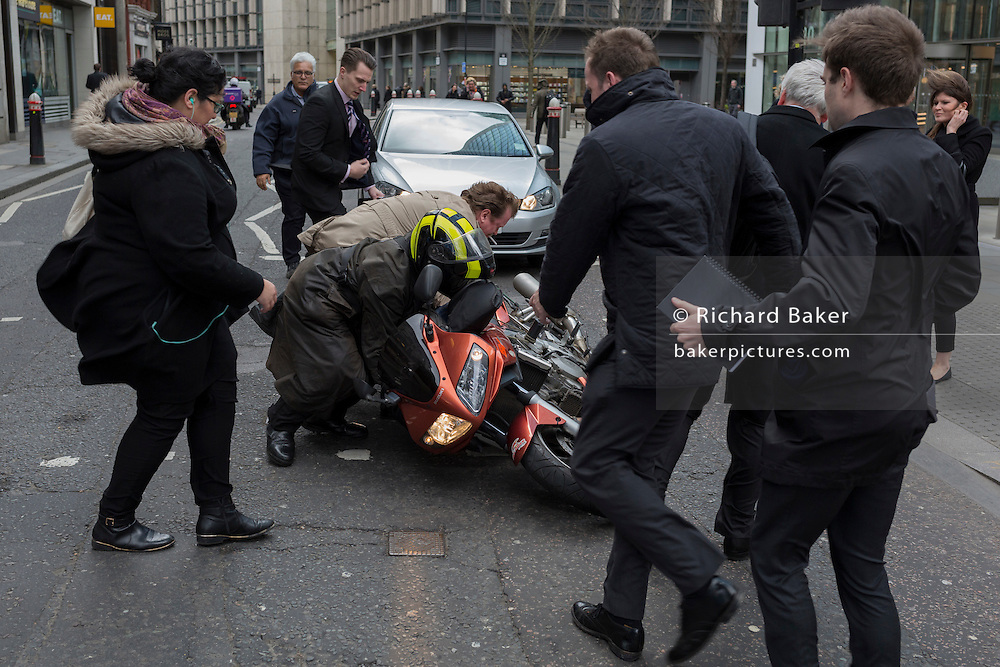 Strangers help a motorcyclist after he was blown over in wind gusts as Storm Doris blows across the UK and pedestrians brave the high winds funneled through the narrow streets, squeezed between the tall buildings of financial and insurance institutions in the City of London, on 23rd February 2017. Strong winds have led to flight cancellations and road and rail disruption across much of Britain. Thousands of homes have been left without power in Northern Ireland, Wales, Scotland and northern England.