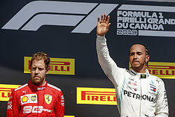 June 9, 2019, Montreal, Canada: Unhappy Scuderia Ferrari driver SEBASTIAN VETTEL, left, of Germany sulks as race winner LEWIS HAMILTON of Mercedes AMG waves on the podium after the Formula One Grand Prix of Canada. Vettel finished in the lead, but was relegated to second place by a 5-second penalty he received for returning to the track in an 'unsafe' manner after a mid-race mistake. (Credit Image: © Hoch Zwei via ZUMA Wire)