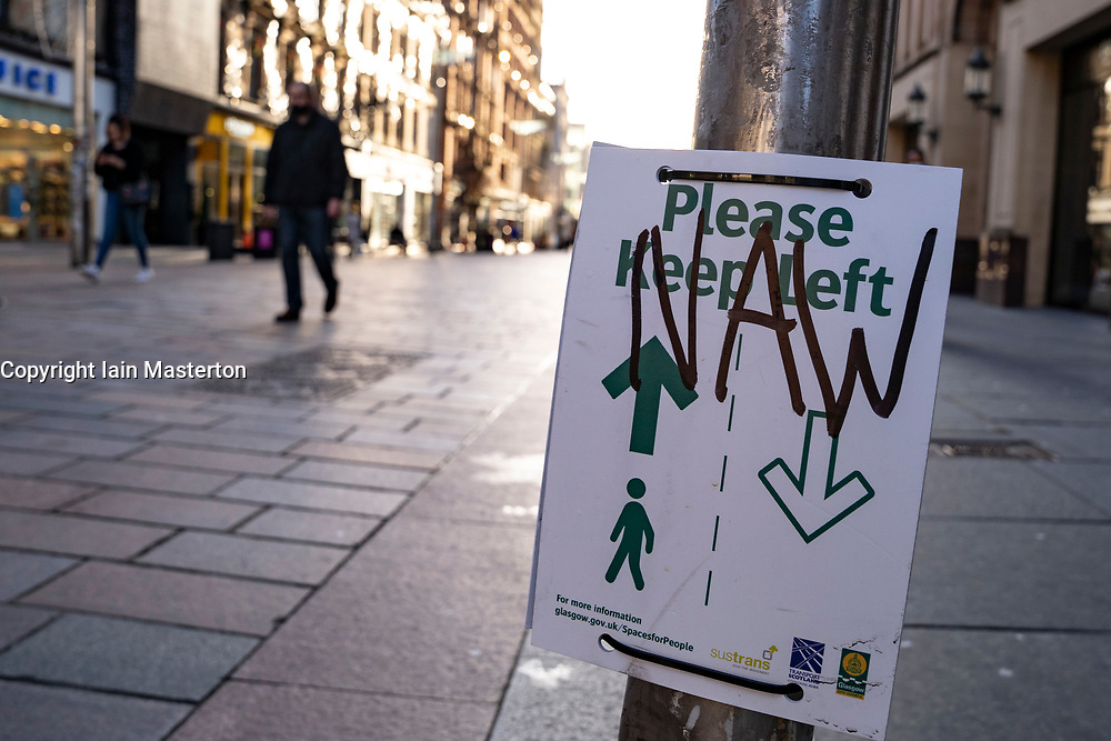 Glasgow, Scotland, UK. 25 November 2020. Glasgow city centre  very quiet during severe level 4 lockdown imposed by the Scottish Government.  Non essential businesses , bars, restaurants and shops are closed. Pictured; Social distancing sign has been vandalised. Credit.  Iain Masterton