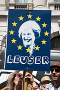 On 2nd anniversary of Brexit , June 23rd 2018, around 100,000 people marched in Central London demanding a People's Vote on the final Brexit deal. A woman holds a placard with a picture of Theresa May on a blue background with a ring of yellow stars aound her face and the word Leuser underneath.