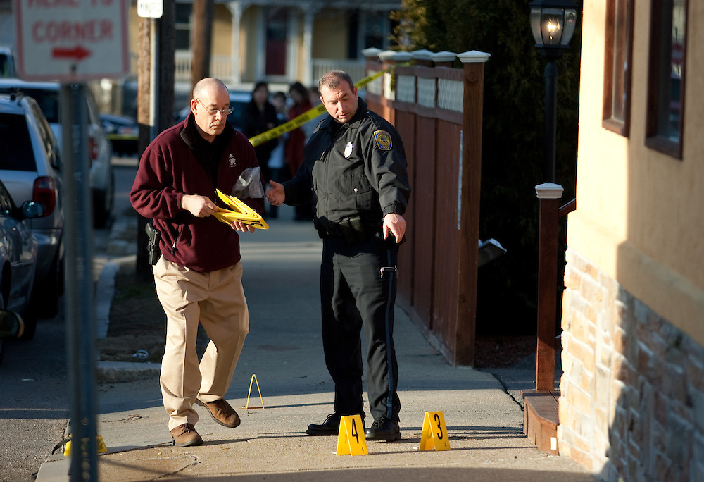 Newton, MA 03/17/2011.Newton Police officers place evidence markers on shell casings on the sidewalk outside of Cristofari Jewelers after an assailant fired 8 shots through the front door of the business on Thursday afternoon..Alex Jones / For The Newton TAB